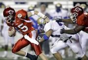 Utah quarterback Brett Ratliff, left, tries to escape Tulsa linebacker Alain Karatepeyan as Utah lineman Zane Beadles, right, tries to block in the first half. Utah beat Tulsa, 25-13, in the Armed Forces Bowl on Saturday in Fort Worth, Texas.
