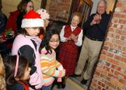 Ray and Marion Wilbur applaud the Carttar family group after their Christmas carol performance Saturday night outside the Wilburs' home. Spreading holiday cheer through caroling has become a Carttar family tradition.