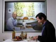 Accenture researchers Dadong Wan, right, and Adam Pilon demonstrate a video conferencing device Dec. 15 that allows families to dine together from different locations.