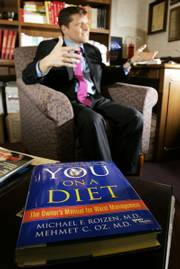 "Dr. Michael F. Roizen and book collaborator, Dr. Mehmet C. Oz&squot; book ""You on a Diet"" rests on a table in Roizen&squot;s office as Roizen gives an interview at the Cleveland Clinic. Roizen is 60, but by the standards of his RealAge test, he&squot;s the equivalent of a 42-year-old, perhaps a few months younger."
