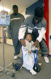 Missouri defensive lineman Jamar Smith, right, places a Tigers T-shirt on the shoulders of 23-month-old Dylan Ruiz during a visit by the team to the pediatric ward at Thomason Hospital. MU visited the El Paso hospital on Tuesday, three days before its Sun Bowl meeting with Oregon State.
