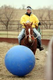 Janise Elder, Overland Park, and her horse Snickers dribble an inflatable ball along the fence line of a corral during a game at stables near Edgerton.