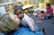 Terionna McIntyre, 5 months, gets a kiss from Robin Barber, director of Kindercare Learning Center, 2333 Crestline Drive, Thursday afternoon in the infant room of the center as Jasmy Mavilla, 9 months, plays with teacher Whitney Blake. The center is one of several in Lawrence that offer child care.