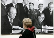 Judy Plumley, of Brighton, Mich., views a photograph of President Gerald Ford, left, and Soviet leader Leonid Brezhnev meeting in November 1974 in Vladivostok, Russia. The picture is in the Gerald R. Ford Presidential Library in Ann Arbor, Mich. Ford, the 38th U.S. president, died Tuesday at 93. 