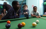 Stephan Fulton, 10, lines up his shot as he plays a game of pool with Dachae Atkins, 9, left, and his cousin Kendrick Atkins, 7, right, during an overnight New Year's party for local children at the Holcom Park Recreation Center, 2700 W. 27th St. Kids ages 5-12 enjoyed games, pizza, and various other activities during the all-night party.