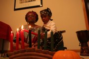 Maren Turner of Lawrence explains the meaning behind Kwanzaa traditions as Kalia Fowler, 6, lights the ceremonial candles. Turner welcomed nine guests for a Karamu feast to celebrate Kwanzaa on Sunday night at her home.