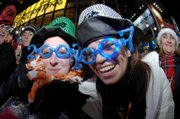 Leanne Cox, left, and Katie Surridge, both of Liverpool, England, show off their 2007 glasses while joining hundreds of thousands of New Year's Eve celebrants in Times Square on Sunday in New York.