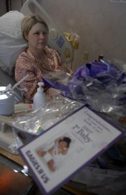 Dee Steinle rests in Lawrence Memorial hospital's maternity ward Tuesday, with baskets of gifts given to her daughter, Nora Katherine, who was born  at 12:29 a.m. on New Year's Day. Nora was sent to Children's Mercy Hospital in Kansas City, Mo., to be treated for oxygen deprivation.