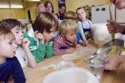 Children look on as an instructor in a kids cooking class mixes dough. The class met at King Arthur Flour in Norrwich, Vt.