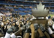 university of cincinnati football players celebrate with the International Bowl trophy. The Bearcats beat the Western Michigan Broncos, 27-24, Saturday in Toronto.