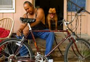 Lawrence resident Louis Galloway works on his bicycle as his dog, Nino, lets out a yawn on the front porch of Galloway's residence in this April 2006 Journal-World file photo. Galloway was standing trial on a charge of aggravated battery when a witness who was scheduled to testify against him was shot Dec. 19 in Ottawa.
