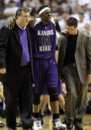 kansas state standout bill walker (12) is helped off the court by coach Bob Huggins, left, and assistant trainer Corey Driskill, right, after being injured during the first half of their game against Texas A&M. Walker played just five minutes in A&M's 69-65 victory Saturday in College Station, Texas.