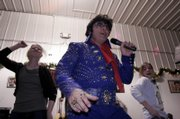 "Elvis tribute artist Tony Aversa, Lawrence, belts out the King&squot;s ""Burnin&squot; Love"" with help from audience members Kelly Morgan, left, and Lisa Lord, both of Lawrence.  The number was one of several dozen delivered during a two-hour performance at Steve&squot;s Place on Saturday night."