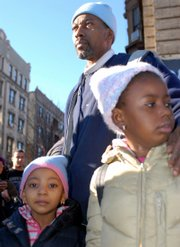 Wesley Autrey stands with his two daughters Syshe, 4, left, and Shuqui, 6, at the Broadway and 145th Street subway stop in New York shortly after he saved the life of a teenager who fell onto tracks in front of an oncoming train Tuesday.
