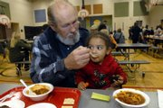 Gary Roit, left, feeds his granddaughter, Sarah Turner, 2, a mouthful of chili Tuesday at New York School during the Martin Luther King Jr. Chili Feed.