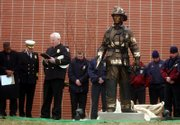 Paul Taylor, Lawrence fire department chaplain, says a prayer outside Lawrence Fire Station No. 5 after the unveiling of Benjamin Victor's sculpture. Victor, of South Dakota, attended the unveiling with his son Caleb, 5. The sculpture was unveiled Saturday.