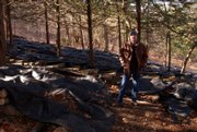 Alan Terry stands amid a sea of shiitake logs on his wooded Baldwin City property. Terry injects the oak logs with mushroom spores, which spread the length of the wood while sitting for a couple of years and then sprout fruit.