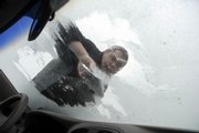 Matt Brown, a resident assistant at Kansas University's Hashinger Hall, scraped ice from his windshield earlier this month. Brown knows about dealing with ice and snow - he's from Grand Forks, N.D. A professor at Dartmouth College has created a way to make ice fall from a specially treated vertical surface.