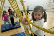 "Langston Hughes School kindergartner Lauren Hoppe climbs across a net during a game of ""swamp"" in the school gymnasium. Gov. Kathleen Sebelius wants to gradually phase in all-day kindergarten classes over the next five years in Kansas public schools. In Lawrence, more specifics on funding are needed before the district can determine how widespread the implementation might be."