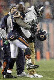Chicago running back Thomas jones (20) lifts coach Love Smith at the end of the NFC championship game. Smith became the first black head coach to qualify for the Super Bowl and was followed hours later by Indianapolis' Tony Dungy.