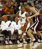 Texas' brittainey raven moves around the defense of Texas A&M's Jennifer Wilks in the second half. No. 22 Texas beat No. 17 Texas A&M, 64-45, Sunday in Austin.