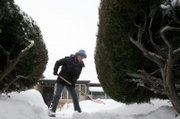 Terri Anderson clears a walkway of an elderly neighbor Sunday in Denver. The latest in a series of winter storms battered Colorado on Sunday, dumping several inches of snow and creating whiteout conditions on the state's eastern plains.