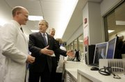 President Bush tours the emergency room Thursday at St. Luke's East Hospital in Lee's Summit, Mo. At left is Jim Hart, of St. Luke's Health System.