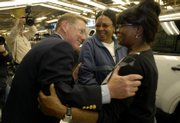 Alan Mulally, president and CEO of Ford Motor Co., stops on the assembly line to visit with employees Arlene Buford, center, and Kay Marshall during a tour of the Ford Kansas City Assembly Plant in Claycomo, MO. Mulally, who grew up in Lawrence, was at the plant Friday to celebrate production of the 2008 Ford Escape and the Mercury Mariner.