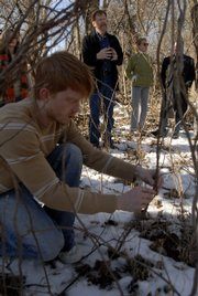 KU sculpture student Whit Bones weaves together some vines Friday morning where he is planning a sculpture along the Kansas River in Burcham Park. In the background, artist John Hachmeister talks about a proposal to turn part of the river bank near downtown Lawrence into a sculpture garden.