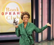 "In this photo provided by Harpo Productions Inc., talk show host Oprah Winfrey holds a copy of her book club choice, Sidney Poitier&squot;s autobiography ""The Measure of a Man,""  during Thursday&squot;s taping of ""The Oprah Winfrey Show"" in Chicago."