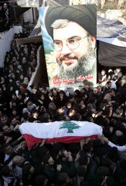 Relatives of Adnan Shams, 25, who was killed during Thursday's confrontations that erupted between government and opposition supporters, carry his coffin next to a poster of Hezbollah leader Sheik Hassan Nasrallah during Shams' funeral procession Friday in Beirut, Lebanon.