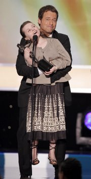 "Greg Kinnear holds up Abigail Breslin as she accepts the award for outstanding performance by a cast in a motion picture for their work in ""Little Miss Sunshine."" The cast included Breslin, Kinnear, Steve Carell, Toni Collette and Alan Arkin."