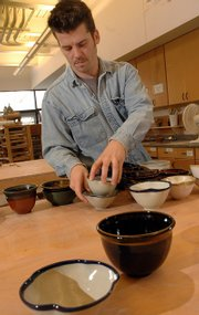Ben Ahlvers, education coordinator at the Lawrence Arts Center, sets out handmade ceramic bowls for the center's Souper Bowl last year. More than 500 bowls will be available for purchase again this year - with a serving of soup and bread - to raise money for the center's ceramics program.