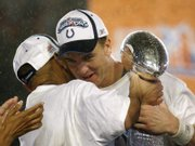 Indianapolis quarterback Peyton Manning, right, hugs coach Tony Dungy as they hold the Lombardi Trophy. Manning was named MVP of the Colts' 29-17 Super Bowl victory against the Bears on Sunday in Miami.