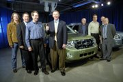 Alan Mulally, president and chief executive officer of Ford Motor Co., center, gives a thumbs-up to the crowd during a visit in January to the Kansas City Assembly Plant to celebrate production of the 2008 Ford Escape and the Mercury Mariner. Mulally plans to visit Lawrence next month to serve as grand marshal for the city's St. Patrick's Day Parade.