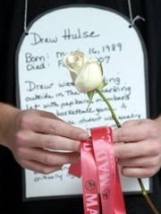 "A Lawrence High School student wears a black shirt and a tombstone and holds a rose to represent being killed in a drunken driving accident. About 55 students participated in a program called ""Every 29 Minutes"" to educate their classmates about the dangers of drunken driving."