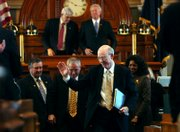 After delivering a message about agro-defense to both the Kansas House and Senate, Senator Pat Roberts waves as he exits the House Chambers in Topeka.  Roberts, pictured on Monday, is leading an initiative to draw in a national agro-defense facility to Kansas.  Clockwise from top left in background is House Speaker Melvin Neufeld, R-Ingalls, Senate President Stephen Morris, R-Hugoton, Rep. Barbara Ballard, D-Lawrence, Rep. Mike Oneal, R-Hutchinson, and Larry Powell, R-Garden City.