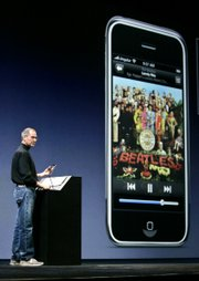 "Apple CEO Steve Jobs plays a Beatles Song from the ""Sgt. Pepper&squot;s"" album on iTunes as he introduces the new iPhone at MacWorld in San Francisco in this Jan. 9 file photo. Apple said Monday that it settled long-simmering trademark issues with The Beatles&squot; Apple Corps Ltd. company about the use of the name ""Apple"" and apple logos."