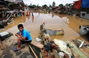An Indonesian boy sits amid the ruins of houses destroyed by flooding in Jakarta, Indonesia. Boats ferried emergency supplies to desperate residents of Indonesia's flood-stricken capital Monday as overflowing rivers again burst their banks following days of rain.