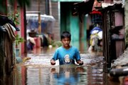 An Indonesian boy wades through floodwater in Jakarta, Indonesia. Overnight downpours sent storm waters coursing back into many low-lying areas of Indonesia's capital on Tuesday, adding to the misery of some 340,000 people forced from their homes by days of flooding, witnesses and officials said.