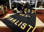 Below, archivist greg kinney unrolls the 1993 NCAA Tournament finalist banner on Tuesday at the University of Michigan Bentley Historical Library in Ann Arbor, Mich., where the banner has been kept since it was removed from Crisler Arena in 2002.
