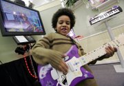 Jalen Stewart demonstrates the I Can Play Guitar System from Fisher-Price during the American International Toy Fair last week in New York. The lead guitar plugs into a television and contains the software necessary for the interactive learning and playing experience. It will retail for $99.99 in July. Fisher-Price is a division of Mattel.