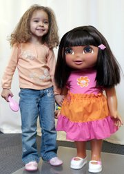 Model Bailey Bass, 3, poses with a life-sized Dora from Fisher-Price. Squeeze the hand of the 34-inch-tall doll, and she can respond with phrases in Spanish and English.
