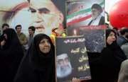 With a photo of Iran's late leader Ayatollah Khomeini in the background, Iranian protesters hold pictures of Iran's supreme leader Ayatollah Ali Khamenei. Thousands attended a demonstration to mark the 28th anniversary of the Islamic Revolution on Sunday in Tehran.