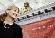Newly appointed President of Harvard University Drew Gilpin Faust stands beneath a bust of university founder John Harvard after a news conference Sunday in Cambridge, Mass. Faust had been dean of Harvard's Radcliffe Institute for Advanced Study since 2001.