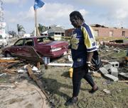 Hellean Lewis walks away from a home that was destroyed by an early morning tornado in New Orleans. Lewis' neighbor, Stella Chambers, died Tuesday after the twister slammed into her trailer, ripping it and her newly renovated home apart and scattering debris about 200 feet to the Industrial Canal levee.