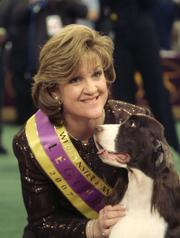An English springer spaniel named Diamond Jim, also known as James, poses with his handler Kellie Fitzgerald after winning best in show Tuesday at the 131st Westminster Kennel Club dog show in New York City.