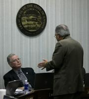 Kansas State Board of Education Chairman Bill Wagnon, left, and board member Kenneth Willard discuss science standards after the board adopted new, evolution-friendly science standards for Kansas public schools in a 6-4 vote. Wagnon voted Tuesday for the standards and Willard voted against them, as the board changed the science standards for the fifth time in eight years.