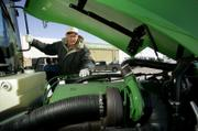 Farmer Vance Ehmke looks at the engine in a new tractor earlier this month at a John Deere dealership in Leoti. With higher crop prices and a break in drought conditions, many farmers are in the market for new equipment.