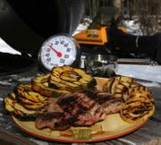 "Grilled pork chops with squash, apples and cider-bourbon jus from Karen Adler and Judith Fertig's ""Weeknight Grilling with the BBQ Queens"" is perfect for those who can't go without grilling during a long winter."